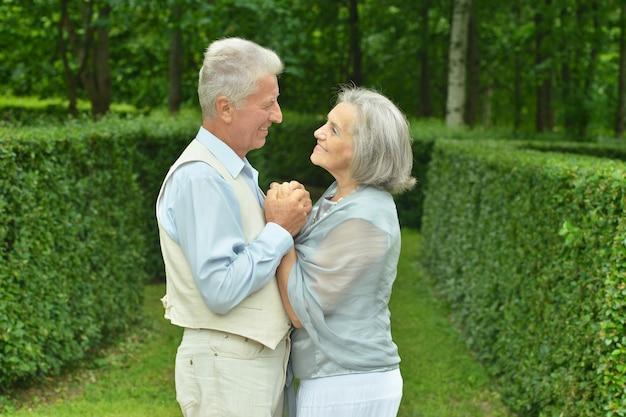 Vecchia coppia innamorata che cammina nel parco in primavera