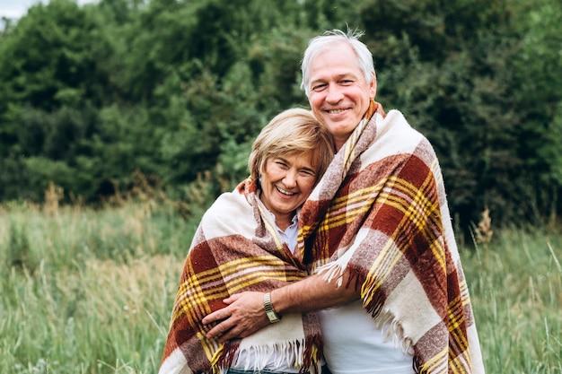 La vecchia coppia cammina nella natura, si tiene per mano, si coccola