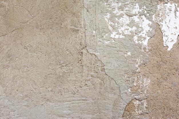 Vecchio intonaco incrinato su un muro di mattoni con peeling vernice bianca