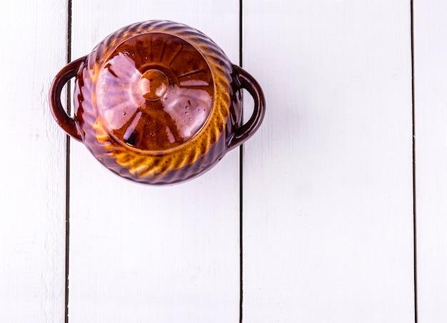 Vecchia pentola di coccio che cucina sulla tavola di legno bianca. vista dall'alto