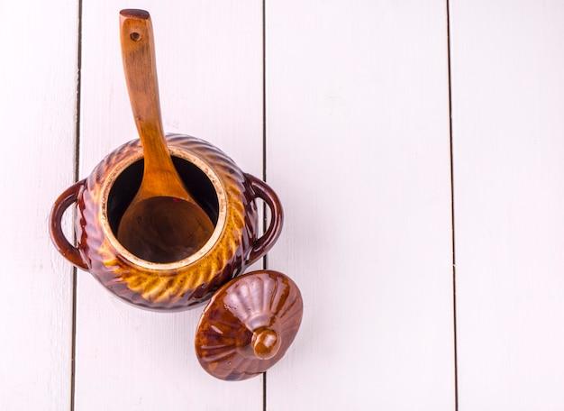Vecchia cottura della pentola di coccio e cucchiaio di legno sulla tavola di legno bianca. vista dall'alto