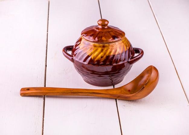 Vecchia cottura della pentola di coccio e cucchiaio di legno su fondo di legno bianco