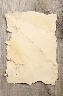 Vecchia carta stropicciata su uno sfondo di legno