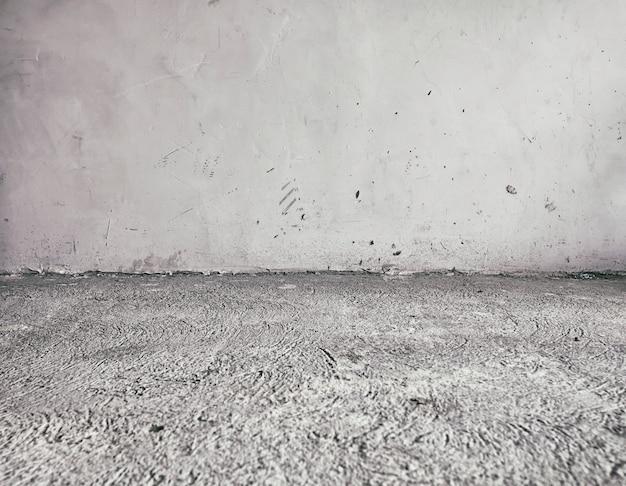 Pavimento in cemento vecchio e sporco e parete grigia coperta casa abbandonata