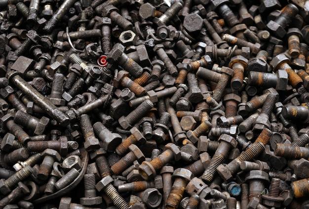 Vecchia vite arrugginita sporca, bullone, perno di metallo e fondo delle noci del metallo.