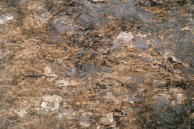 Vecchio primo piano graffiato sporco di struttura del truciolato