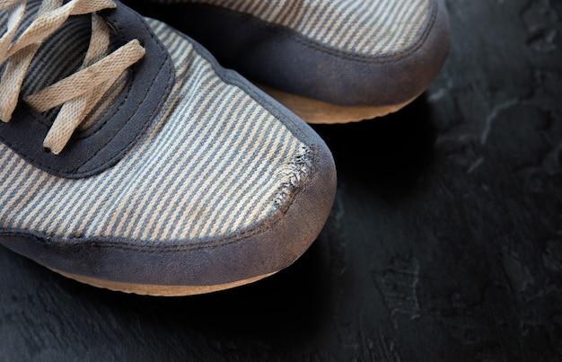 Vecchie scarpe sporche con un buco. allenatori usurati.