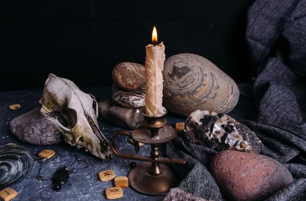 Vecchio teschio di cane candela che brucia rune e pietre di legno sul tavolo delle streghe