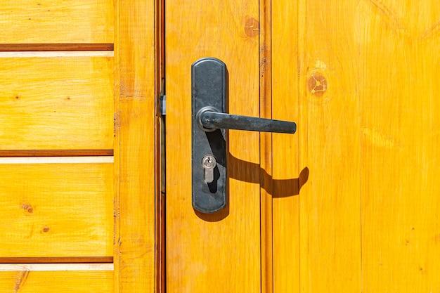 Vecchia maniglia della porta con serratura sulla porta di legno