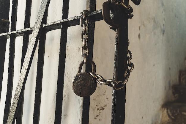 Vecchia porta arrugginita. la vecchia catena del lucchetto blocca un concetto di prigione.