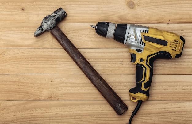 Vecchio trapano avvitatore e martello su uno sfondo di legno. vista dall'alto