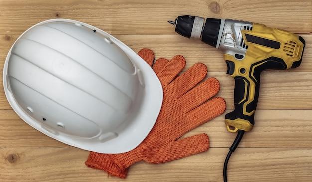 Vecchio trapano avvitatore e casco protettivo, guanti su uno sfondo di legno. vista dall'alto