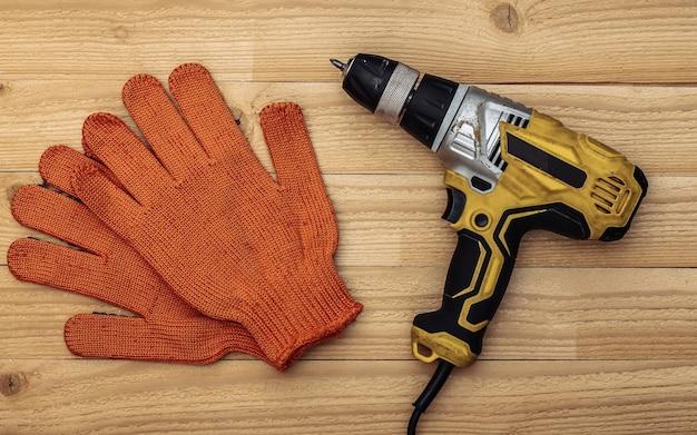 Vecchio trapano avvitatore e guanti da lavoro su uno sfondo di legno. vista dall'alto