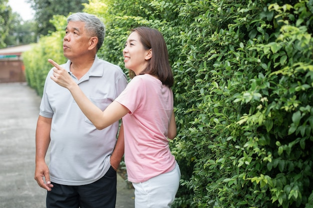 Un vecchio uomo asiatico anziano e camminare nel cortile con sua figlia
