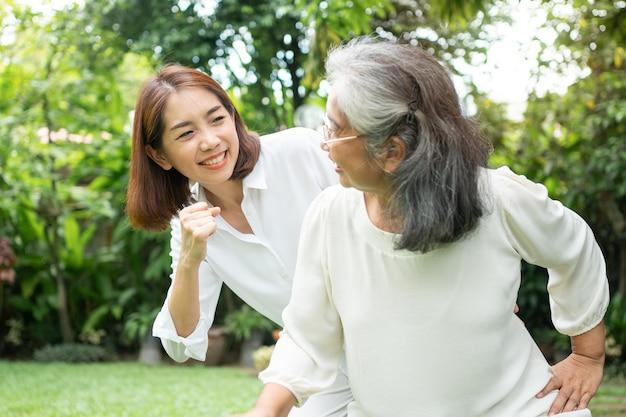 Una donna asiatica anziana anziana ed esercita nel cortile con sua figlia