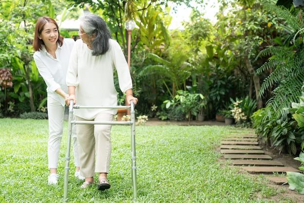 Una vecchia donna asiatica anziana utilizza un deambulatore e cammina nel cortile con sua figlia