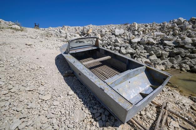 La vecchia barca a motore vuota di pesca del metallo si è messa in bacino vicino al lago o alla riva del mare