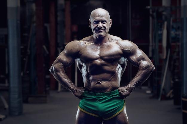 Culturista dell'atleta di vecchia moda che fa gli esercizi del braccio in palestra stile uomo sportivo caucasico calvo brutale degli anni '80. concetto di sport, fitness e allenamento anni '80