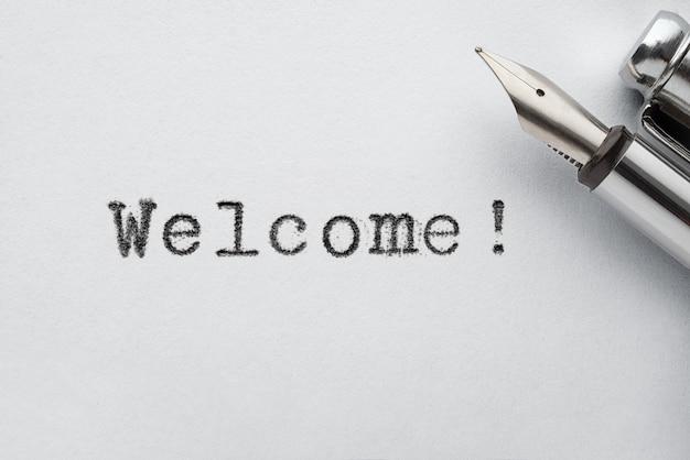 Penna stilografica vecchio stile in acciaio su pagina di carta con parola di benvenuto