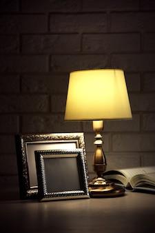 Vecchia lampada da tavolo alla moda sul tavolo su un muro di mattoni