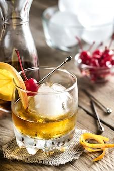 Cocktail vecchio stile con ciliegia e arancia