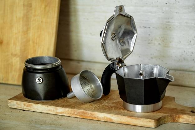 Macchina da caffè geyser smontata vecchio stile sulla scrivania in legno dopo il lavaggio
