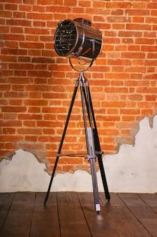 Lampada da terra antiquata su treppiede vicino al muro di mattoni