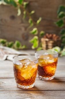 Negroni cocktail italiano antiquato con gin secco, campari, martini rosso vermouth e ghiaccio su un tavolo di legno. bevanda rinfrescante estiva