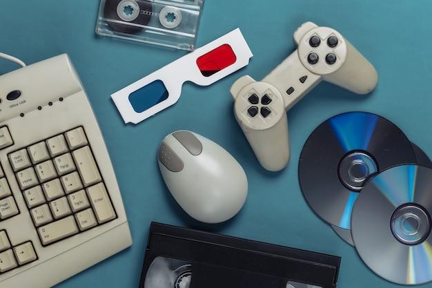 Tastiera antiquata, mouse per pc, compact disc, gamepad, occhiali anaglifi, audio e videocassetta su blu