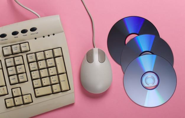Tastiera retrò vecchio stile cd e mouse per pc su pastello rosa