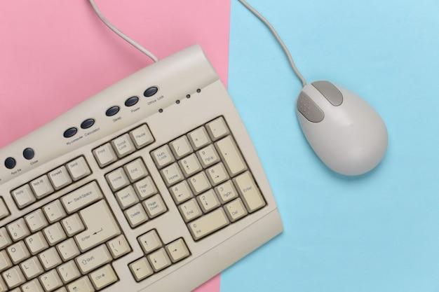 Tastiera retrò vecchio stile e mouse per pc su un pastello blu-rosa. computer retrò