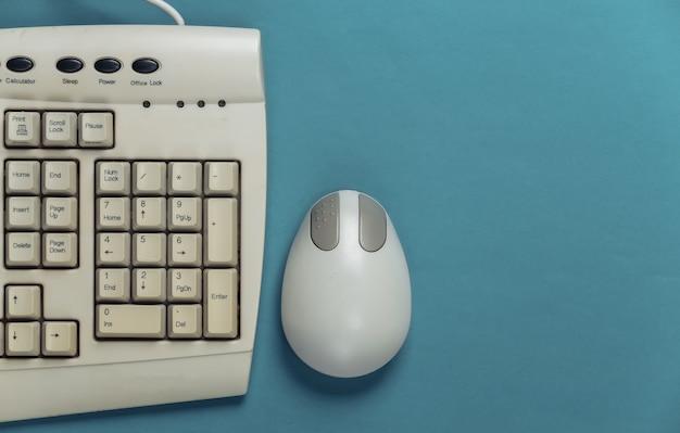 Retro tastiera antiquata e mouse del pc sull'azzurro.