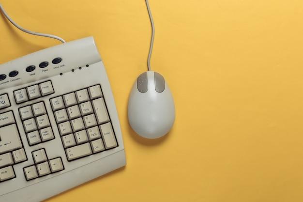 Retro tastiera antiquata e mouse del pc su colore giallo. computer retrò