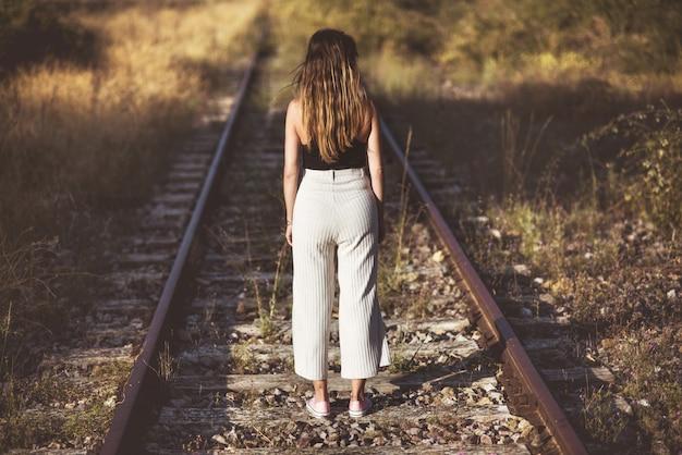 Fotografia di vecchio stile. vista posteriore, di una donna in piedi sui binari del treno.