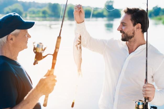 Padre anziano con pesca barbuta del figlio sul fiume.