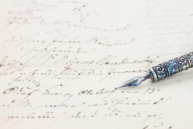Vecchia penna piuma su sfondo lettera scritta a mano