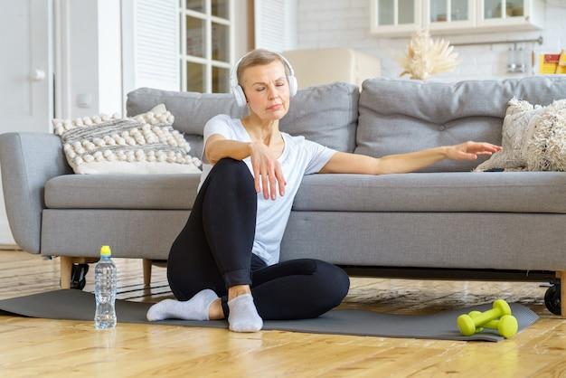Vecchia femmina che si rilassa dopo l'attività di fitness a casa ascoltando musica attività di sollievo dallo stress
