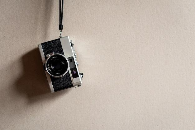Vecchia macchina da presa su fondale in carta color crema. fotocamera analogica con obiettivo 38 mm. fotocamera a telemetro, oggetto vintage e obsoleto