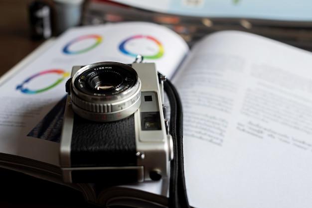 Vecchia macchina da presa a pellicola posizionata sul libro la fotocamera analogica ha obiettivo 38 mm fotocamera a telemetro, oggetto vintage e obsoleto