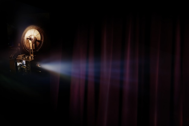Vecchio proiettore cinematografico con sfondo camera oscura