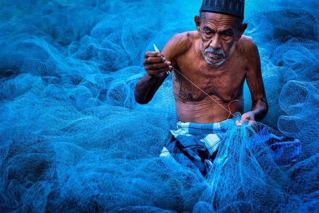 Vecchie mani di pescatori che cuciono reti da pesca blu sedute per terra
