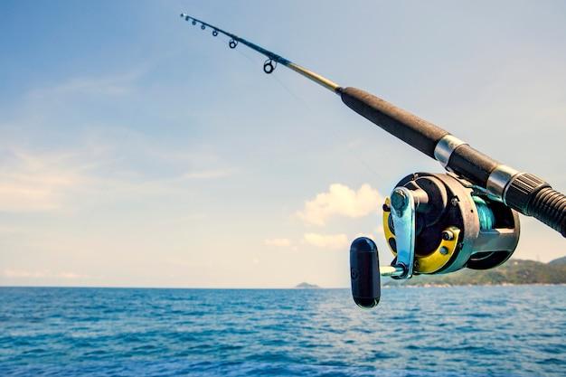 Vecchia canna da pesca e acqua di mare blu