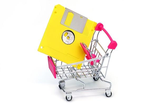 Vecchio floppy disk su un carrello del supermercato sfondo bianco
