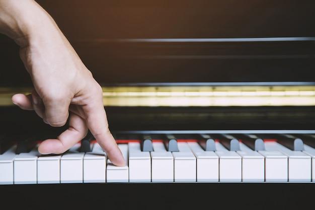Vecchio forte piano con mano femminile e pianista dito anello di diamanti