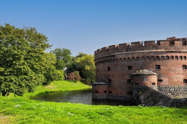 Vecchia fortezza con mattoni rossi e granito, feritoie, fossato d'acqua e un prato con alberi