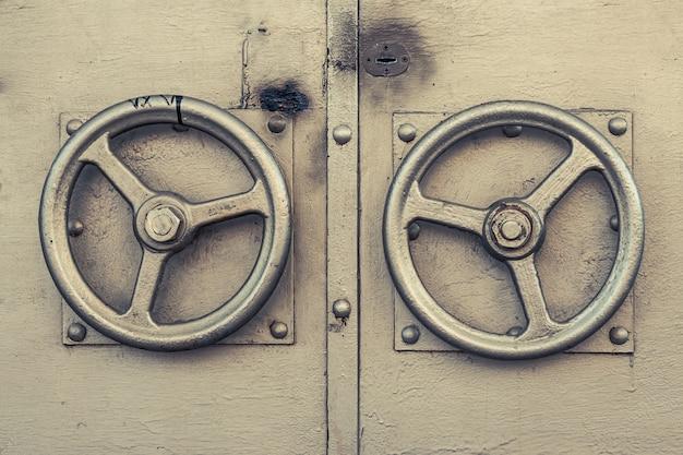 Vecchia porta dorata con due maniglie rotonde.