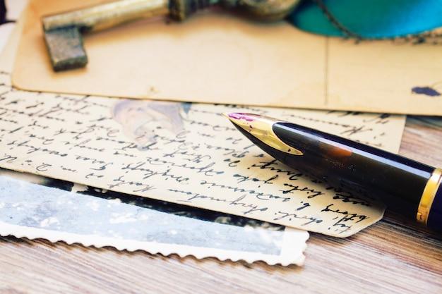 Vecchia penna d'oca dorata e lettere antiche, fuoco poco profondo sulla piuma della penna