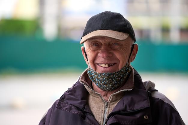 Il vecchio nonno, con indosso una mascherina medica, indossa un cappello, sorride e guarda nella telecamera