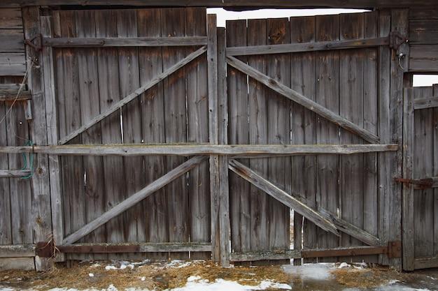 Vecchia porta d'annata grigia della plancia di legno