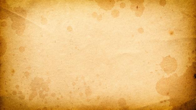 Vecchio sfondo grunge fatto di carta sbiadita malconcia con macchie per il design con spazio per il testo